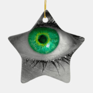 Eye with green iris looks at viewer concept macro ceramic star ornament