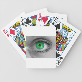 Eye with green iris looks at viewer concept macro poker deck