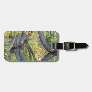 Fall tree trunks with reflection in forest water luggage tag