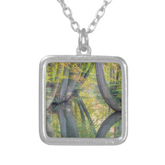 Fall tree trunks with reflection in forest water silver plated necklace