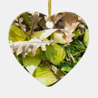 Fallen autumn leaves on green grass lawn ceramic heart ornament