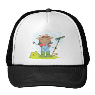 Farmer girl with a rake in grass with flowers trucker hat