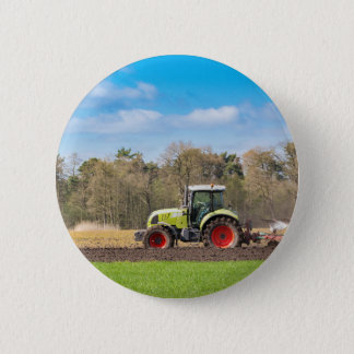 Farmer on tractor plowing sandy soil in spring 2 inch round button