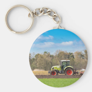 Farmer on tractor plowing sandy soil in spring basic round button keychain