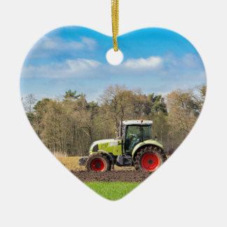 Farmer on tractor plowing sandy soil in spring ceramic heart ornament