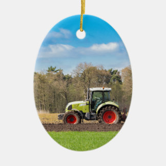 Farmer on tractor plowing sandy soil in spring ceramic oval ornament