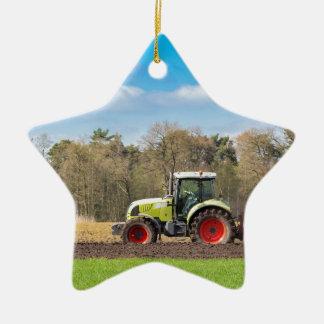 Farmer on tractor plowing sandy soil in spring ceramic star ornament