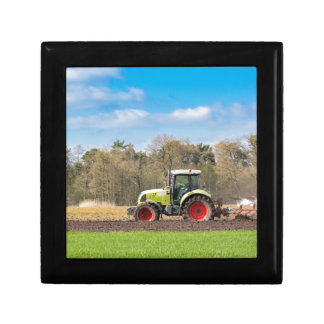 Farmer on tractor plowing sandy soil in spring gift box
