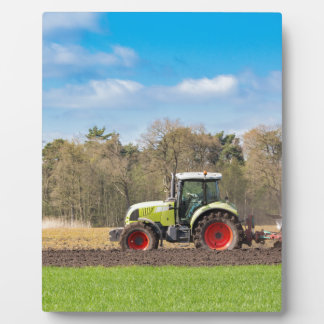 Farmer on tractor plowing sandy soil in spring plaque