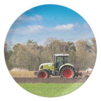 Farmer on tractor plowing sandy soil in spring plate
