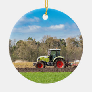 Farmer on tractor plowing sandy soil in spring round ceramic ornament