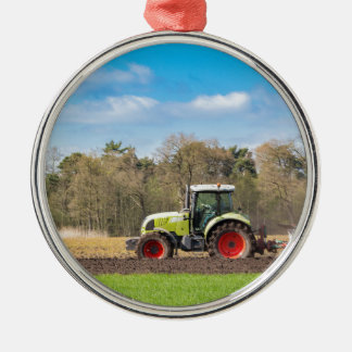 Farmer on tractor plowing sandy soil in spring Silver-Colored round ornament