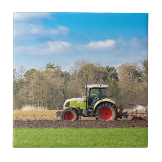 Farmer on tractor plowing sandy soil in spring tile