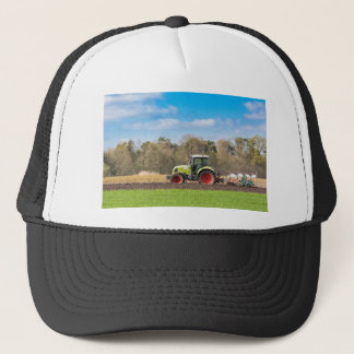 Farmer on tractor plowing sandy soil in spring trucker hat