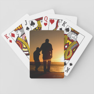 Father and son strolling an the beach poker deck