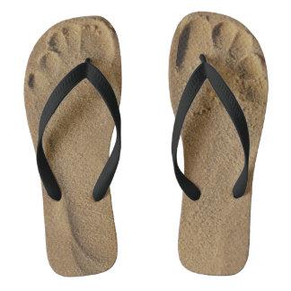 Feet in sand flip flops