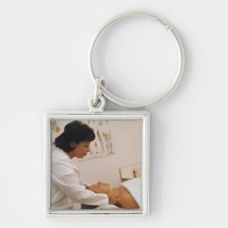 Female chiropractor massaging a patient key chain