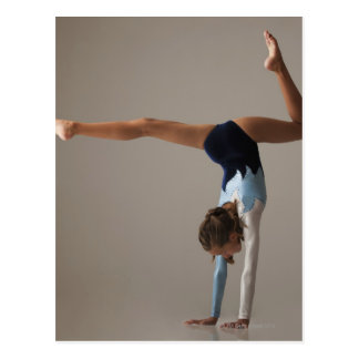 Female gymnast (12-13) performing handstand postcard
