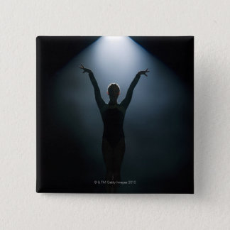 Female gymnast performing in spotlight, studio 2 inch square button