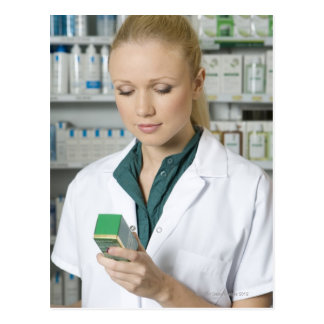 Female pharmacist looking at medicine in postcard