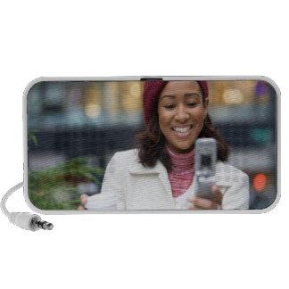 Femme de sourire d'affaires avec le téléphone port haut-parleur ordinateur portable