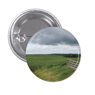 fence gate in front of field with mowed horseshoe 1 inch round button