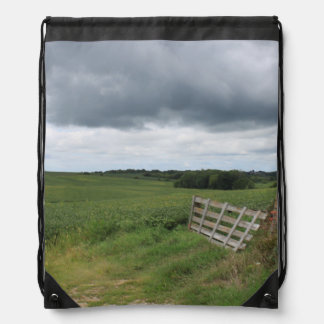 fence gate in front of field with mowed horseshoe drawstring bag