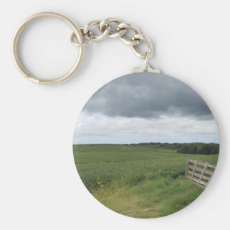 fence gate in front of field with mowed horseshoe keychain