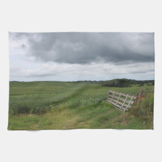 fence gate in front of field with mowed horseshoe kitchen towel