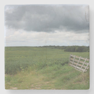fence gate in front of field with mowed horseshoe stone coaster