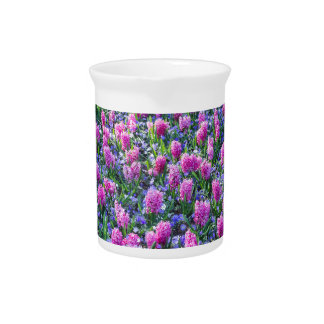 Field of pink hyacinths and red tulips drink pitcher