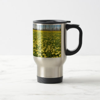 Field of yellow dandelions in grass with tree line travel mug