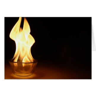 Fire in a bowl isolated in black. greeting card