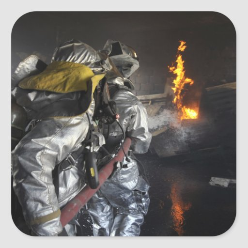 Firefighters extinguish a fire in a training ro square sticker