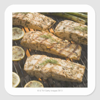 Fish and asparagus cooking on grill square sticker