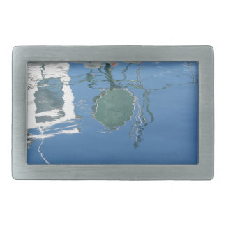 Fishing boat reflects in the water belt buckle