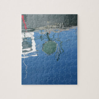 Fishing boat reflects in the water jigsaw puzzle