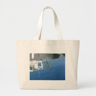 Fishing boat reflects in the water large tote bag