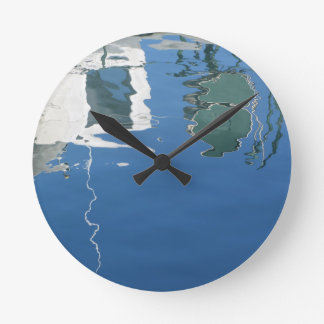 Fishing boat reflects in the water round clock