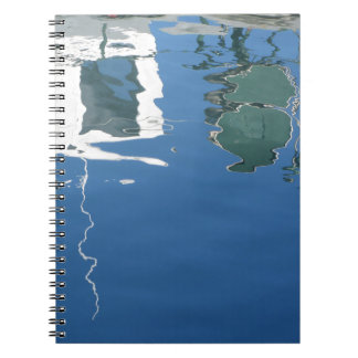 Fishing boat reflects in the water spiral notebook