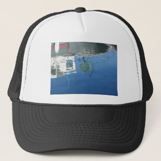 Fishing boat reflects in the water trucker hat