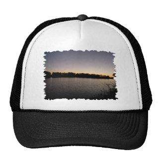 Fishing poles silhouette against the sun set trucker hat