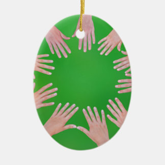 Five children hands joining in circle above green ceramic ornament