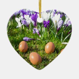 Five loose eggs lying near blooming crocuses ceramic heart ornament