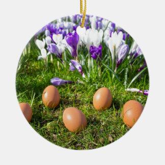 Five loose eggs lying near blooming crocuses round ceramic ornament