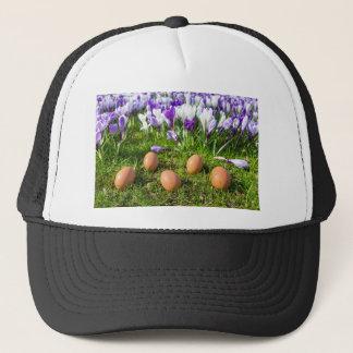 Five loose eggs lying near blooming crocuses trucker hat