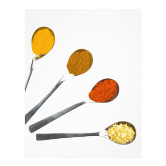 Five seasoning spices on metal spoons letterhead