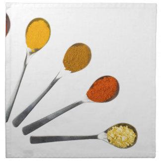 Five seasoning spices on metal spoons napkin