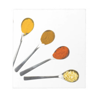 Five seasoning spices on metal spoons notepads