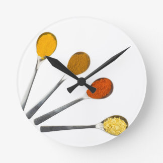 Five seasoning spices on metal spoons round clock